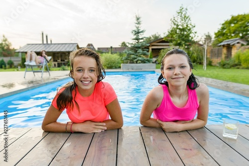 23509c9559149 Two young teen girls having fun in the pool, smiling looking into the camera
