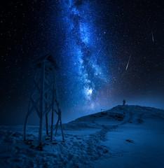 Fototapete - Man looking to falling stars in the mountain in winter