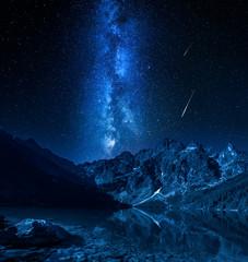 Fototapete - Milky way and falling stars at mountains lake, Poland, Europe