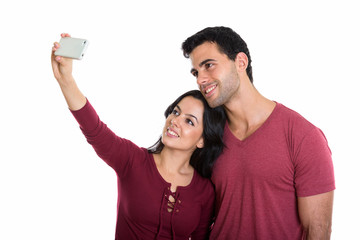 Studio shot of young happy couple smiling while taking selfie pi