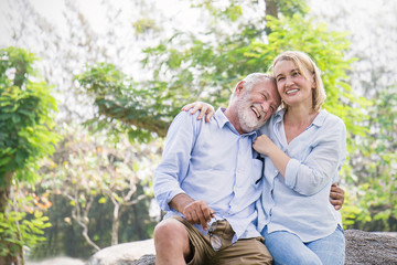 Happy old couple smiling in a park on a sunny day, hoot senior couple relax in the forest spring summer time. Healthcare lifestyle retirement concept