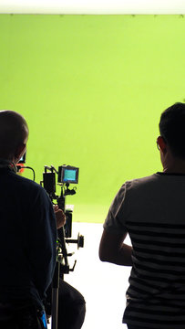 Behind the vdo camera in studio production that shooting or filming green screen background for chroma key technique in post process with professional crew teams and equipments.