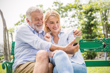 Senior caucasian couple take a self portrait together with smartphone. Closeup old mature man and woman selfie outdoor at the park. People lover lifestyle technology connection network concept