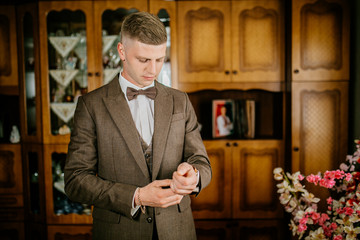 stylish groomsmen helping happy groom getting ready in the morning for wedding ceremony. luxury man in suit in room. Groom preparation before wedding ceremony.