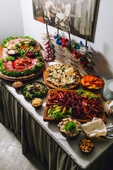 Buffet table of reception with burgers, cold snacks, meat, hum and salads. Tapas bar.