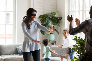 Happy black funny family with little preschool son and daughter spending free time together on weekend at new modern home. Playful mom with covered eyes playing blindman hide and seek in living room