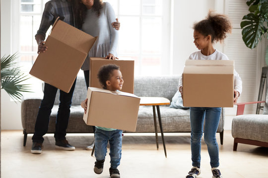 Happy Black African married couple with little kids standing in living room at new home. Small playful adorable kids helps carrying cardboard boxes. New rea estate dwelling, loan and mortgage concept