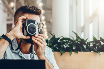 Young bearded man sits in coffee shop at table in front of laptop and takes instant photo on camera.