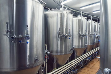 Lines of metal tanks in modern brewery. Shopfloor with brewery facilities. Manufacturable process of brewage. Mode of beer production. Brewing. Inside view of modern beer plant with stainless barrels.