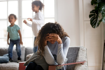 Black single frustrated woman hold her head with hands sitting on chair in living room, playful kids jumping on couch on a background. Tiredness, depression difficult to educate children alone concept