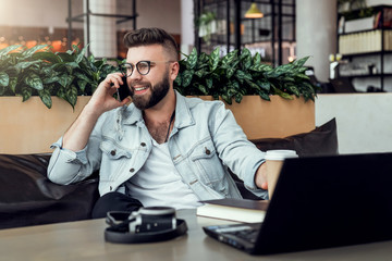 Bearded businessman,blogger sitting in cafe,talking on smart phone,working on laptop, freelancer working in coffee shop.