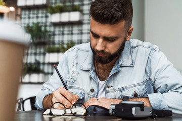 Young bearded hipster man sits in cafe at table,writes in notebook. On table cup of coffee, camera, glasses.Guy working.
