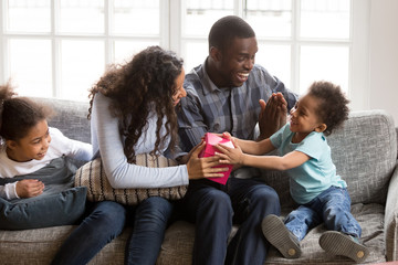 Whole black American family sitting on couch in living room spend time together on weekend at home. Mother helps little adorable son to open pink gift box all family feels happy. Life events concept