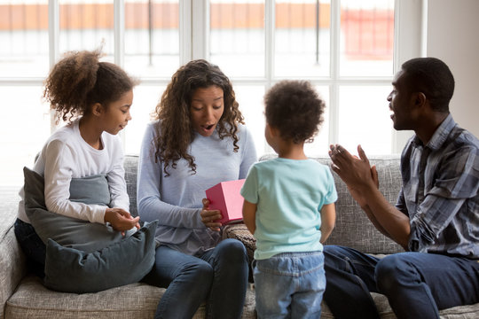 Whole black African family sitting on couch in living room spend time together on weekend at home. Little son gave to mom pink gift box, mother surprised, all family feels happy. Life events concept
