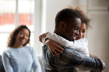 Black African happy family together at home. Close up loving American father strong embrace lovely sweet daughter smiling mother on background sitting on couch. Reunion happy wellbeing family concept