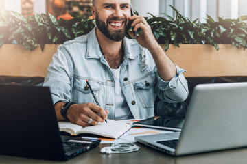 Young bearded cheerful man sits at table in front of laptops, talking on mobile phone while making notes in notebook.