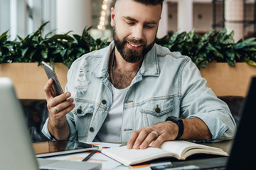 Young bearded hipster man sits in cafe in front of computers, reads notes in notebook while holding smartphone in hand.