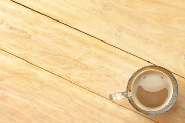Top view picture of clear glass coffee cup with smiling face from creamy coffee froth. Hot coffee in cup putting on right corner of the mirror table and blur wooden floor from the left-handed person.
