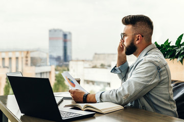 Bearded businessman hipster talking on phone while sitting at desk in office,holds document,sad looking at window.