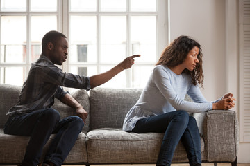 Black married couple sitting on couch in living room at home and quarrelling. Angry husband negative emotionally shouting at wife. Misunderstanding break up problems and trouble in relationship