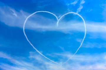 Love picture sign made by aircraft contrail. Image of Heart shaped making from smoke by two small air plane shown on blue sky and white soft clouds.