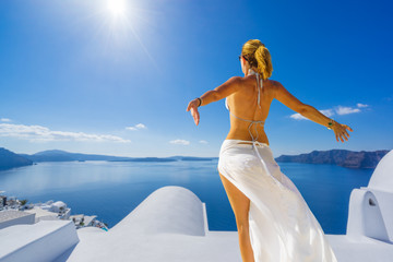 Woman enjoying relaxation in pool and looking at the view in Santorini