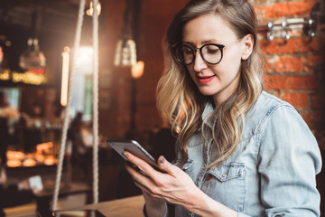 Girl blogger in trendy glasses sits in cafe and uses smartphone,checks e-mail,communicates with followers,reads news.
