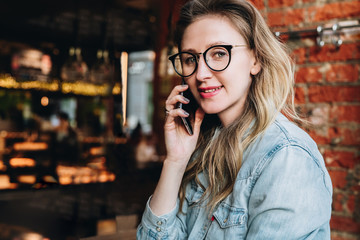 Young businesswoman has telephone conversations.Cheerful girl blogger in trendy glasses sitting in cafe,talking on phone