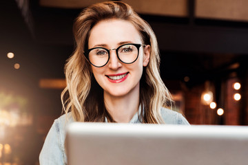 Portrait of young business woman in trendy glasses sitting in cafe,working on laptop.Blogger communicates with followers