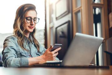 Young businesswoman is sitting in coffee shop at table in front of computer and notebook,using smartphone. Social media.