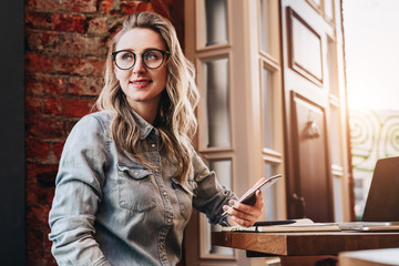 Hipster girl in trendy glasses sits in cafe at table in front of