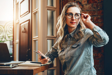 Hipster girl in glasses sits in cafe at table in front of laptop,holding smartphone.Girl looking for friends in cafe.