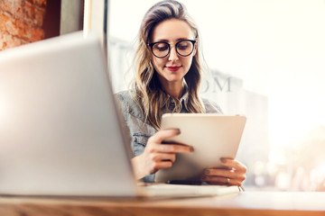 Portrait of young businesswoman in trendy glasses,sitting in cafe in front of laptop, using tablet computer, working.