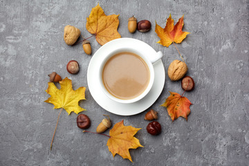 Autumn composition. Cup of coffee, autumn leaves on grey background. Flat lay, top view.