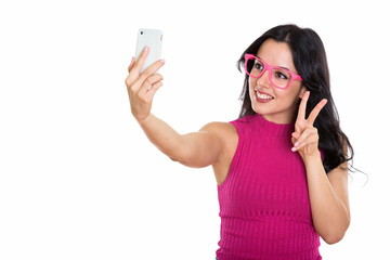 Studio shot of young happy Spanish woman smiling while taking se