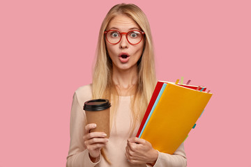Horizontal shot of stupefied blonde woman in red framed eyewear, carries disposable cup of coffee, folders with stickers, feels surprised, isolated over pink background. Omg, I have not time for break