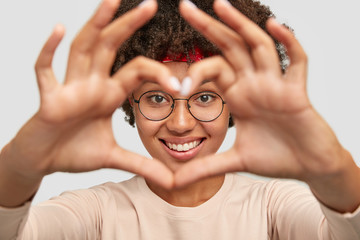 Close up shot of cheerful carefree charming dark skinned girl makes heart shape hand sign over face, demonstrates her love on distance, focus on hands, cares about someone. Romantic affection