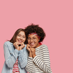 Vertical indoor shot of pleasant looking cheerful mixed race sisters feel support from each other, keep hands together under chin, giggle and stand closely to each other, isolated on pink wall