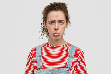 Photo of dissatisfied dejected woman purses lips, frowns face, has spoiled day at university, wears casual jean dungarees, feels lonely, isolated over white studio wall. Facial expressions concept