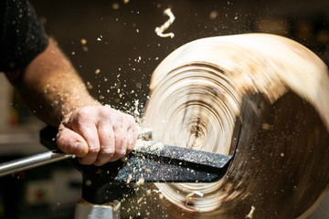 wood working hand edits roating timber with turnery and flying sawdust shavings