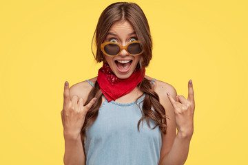 Headshot of provocative cool female hipster shows rock n roll hand gesture, exclaims something loudly, wears fashionable bandana, trendy sunglasses, poses against yellow background. Its so nice!