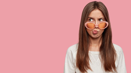 Photo of gloomy woman looks with puzzled negative expression aside, pouts lips with discontent, has dark hair, wears sunglasses, isolated over pink background with free space for your promotional text