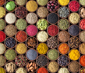 Fototapete - various condiments in cups, food background. Spice texture isolated on black