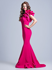 Beautiful young woman in pink fashionable dress.