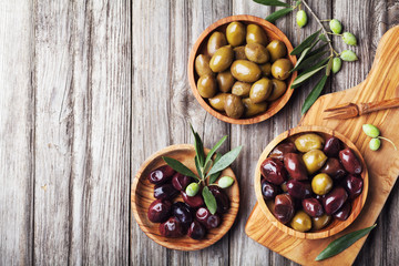 Pickled olives served in bowls from olive wood on rustic kitchen table top view. Wall mural