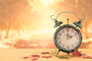 Image of autumn Time Change. Fall back concept. Dry leaves and vintage alarm Clock on rustic wooden table.