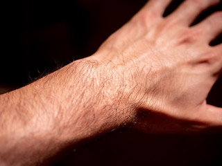 Left hand of young man on black background