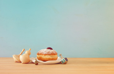 Image of jewish holiday Hanukkah with traditional doughnut and spinning top on the table.