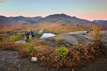 Group of hikers enjoying the viewpoint over Heart Lake in the Adirondacks
