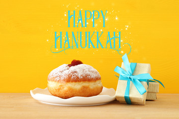 Image of jewish holiday Hanukkah with present box and traditional doughnut on the table.